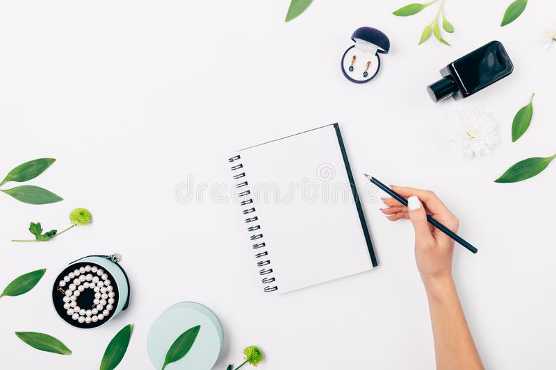 Top view of female hand writing in blank notepad stock image