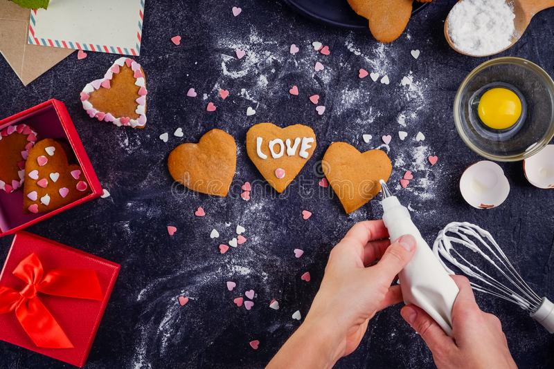 Top view female hands decorating homemade cookies in shape of heart as gift for lover on Valentine`s day. Dark stone background w royalty free stock image
