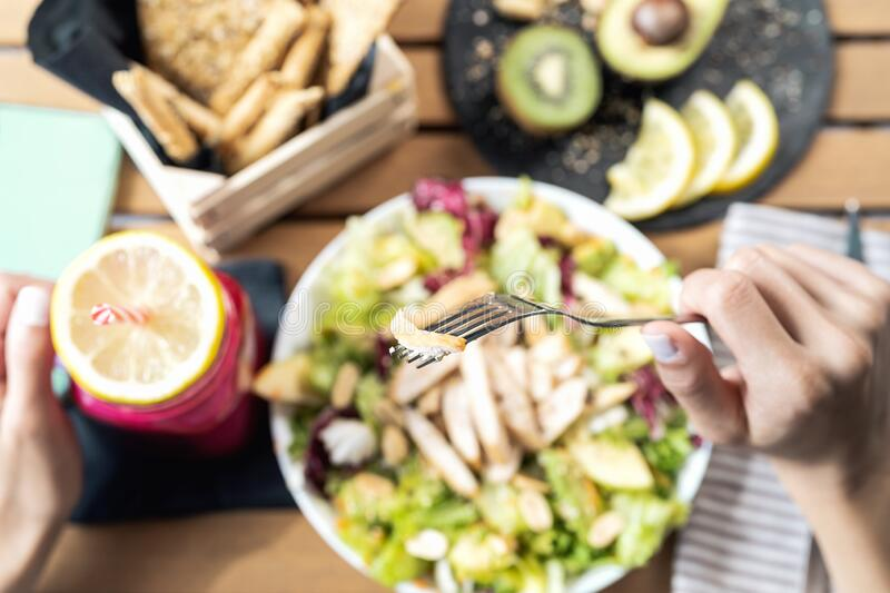 Top view female hands eating health vegetable salad with grilled chicken breast avocado kiwi and drinking fresh smoothie fruits royalty free stock images