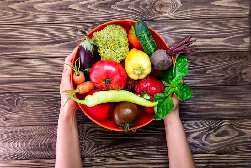 Top view female hands holding the bowl with different Fresh Farm Vegetables on the dark wooden background. Harvest. Food or Health stock images