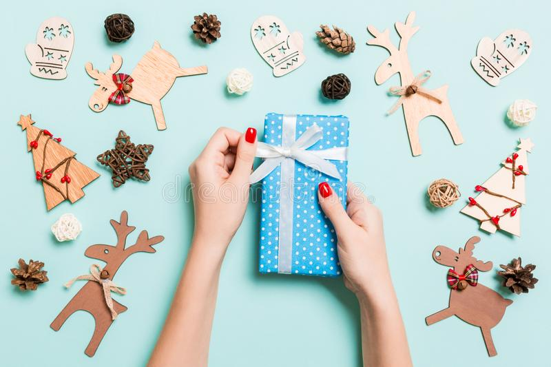 Top view of female hands holding a Christmas present on festive blue background. Holiday decorations and toys. New Year holiday stock photography