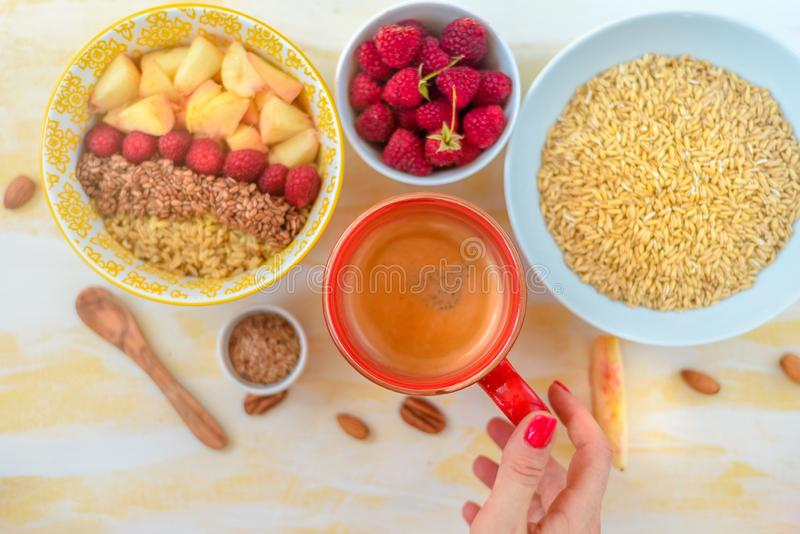 Top view, female hands holding a cup of coffee, a spoon with oatmeal, with honey nuts, raspberries, on a yellow wooden table Good. Morning royalty free stock photo