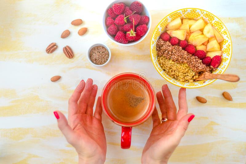 Top view, female hands holding a cup of coffee, a spoon with oatmeal, with honey nuts, raspberries, on a yellow wooden table Good. Morning stock image