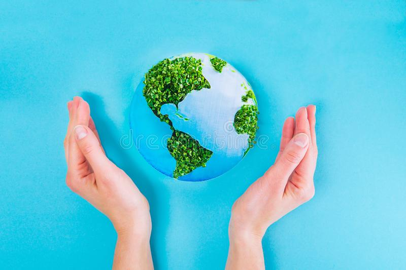Top view Female Hands holding Earth paper and green sprouts collage model on blue background. Earth in your hands, Saving Earth co royalty free stock photos