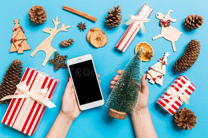 Top view of female hands holding phone in one hand and christmas tree in another hand on blue background. New Year holiday concept royalty free stock image