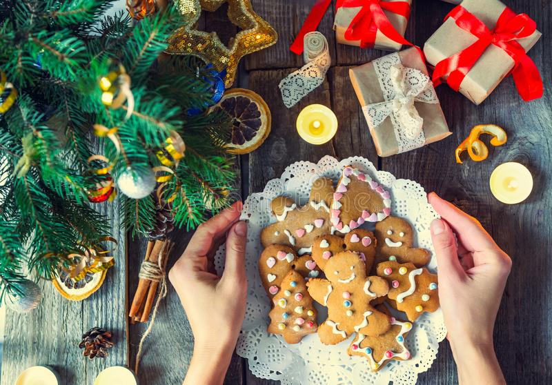 Top view female hands holding plate with homemade gingerbread cookies on the old rustic wooden table with gift boxes, Fir branches stock photos