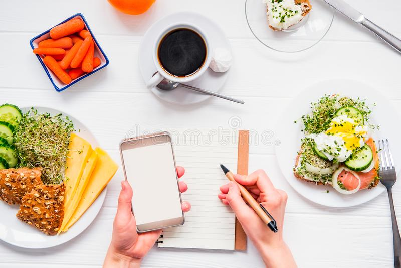 Top view Female hands holding smart phone and writing in notebook on served white wooden table with breakfast dishes. Day diet pla royalty free stock images