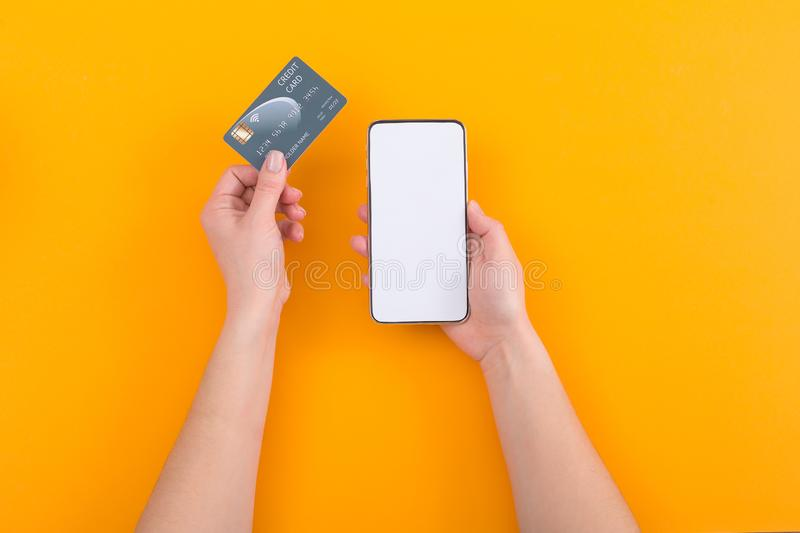 Top view of female hands holding smartphone and credit card on orange background royalty free stock image