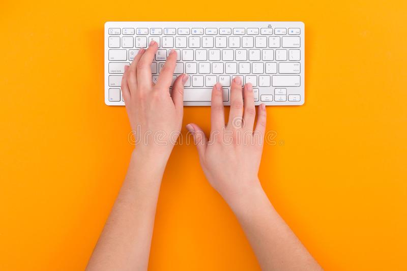 Top view of female hands using computer keyboard while working, orange background. Business concept royalty free stock photography