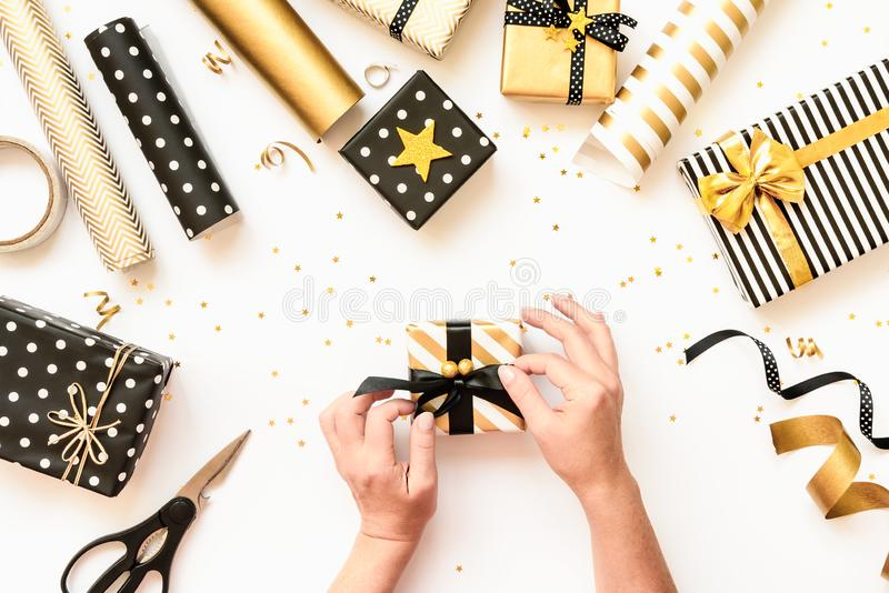 Top view of female hands wrapping gift boxes, scattered wrapping materials in various black, white and golden designs. A concept o royalty free stock image