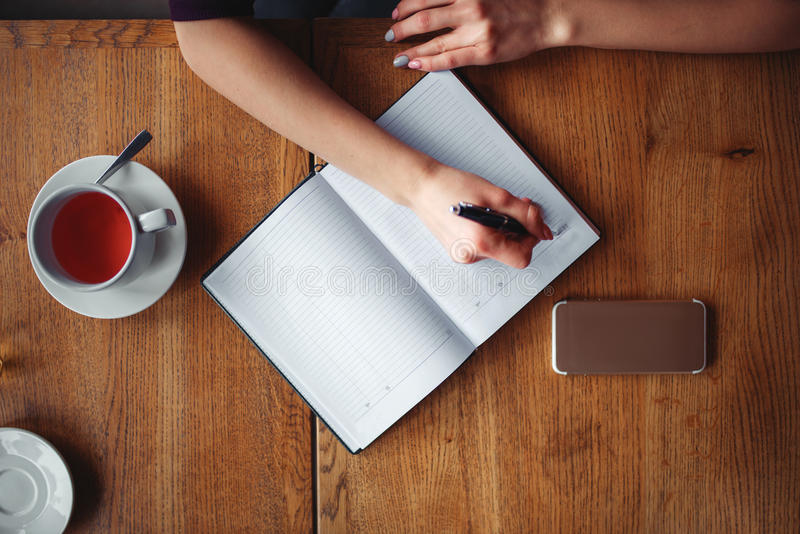 Top view of female hands writing in notebook stock photos