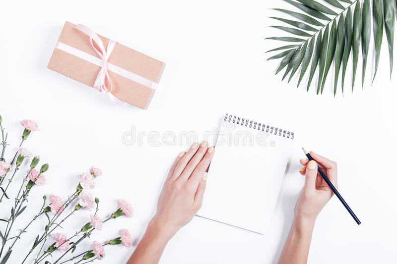 Top view of female hands writing in notepad at the desk stock images