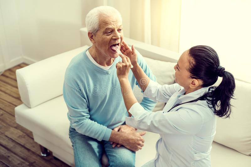 Top view on female nurse checking tonsils of senior patient royalty free stock images
