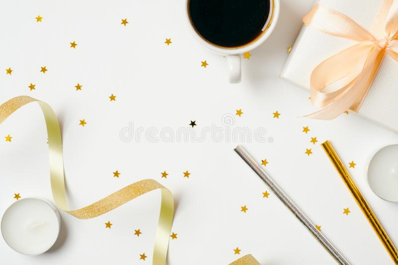 Top view feminine desk with coffee cup and party accessories : ribbon, drink straw, gift box, candles on white background. stock images