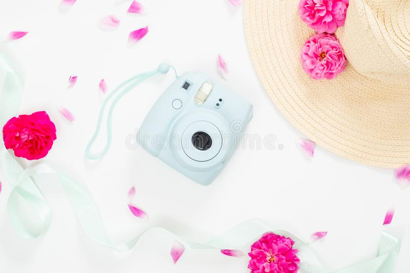 Top view feminine desk with flowers and girl`s stuff. Flat lay modern instant camera, staw hat, ribbon, pink rose flowers on whit royalty free stock images