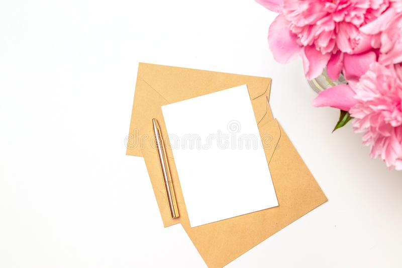Flat lay pion flowers, craft envelope, blank paper card, gift box, ribbon on pink background. Flat lay royalty free stock images