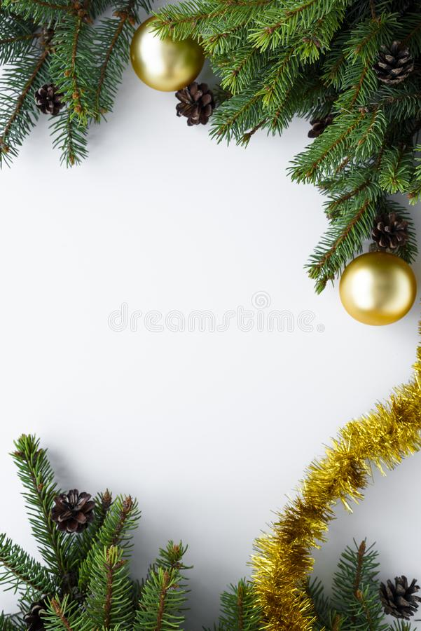 Top view on festive decorations such as gold baubles, tinsel, conifer branches and cones. Christmas vertical greeting card with. Top view on arrangement of royalty free stock photography