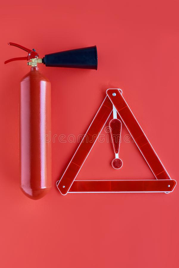 Top view of fire extinguisher and warning triangle. Isolated on red royalty free stock photography