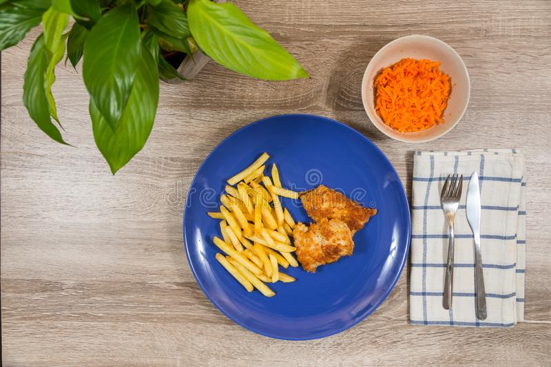 Top view of fish and chips and a bowl carrot salad as a side royalty free stock images