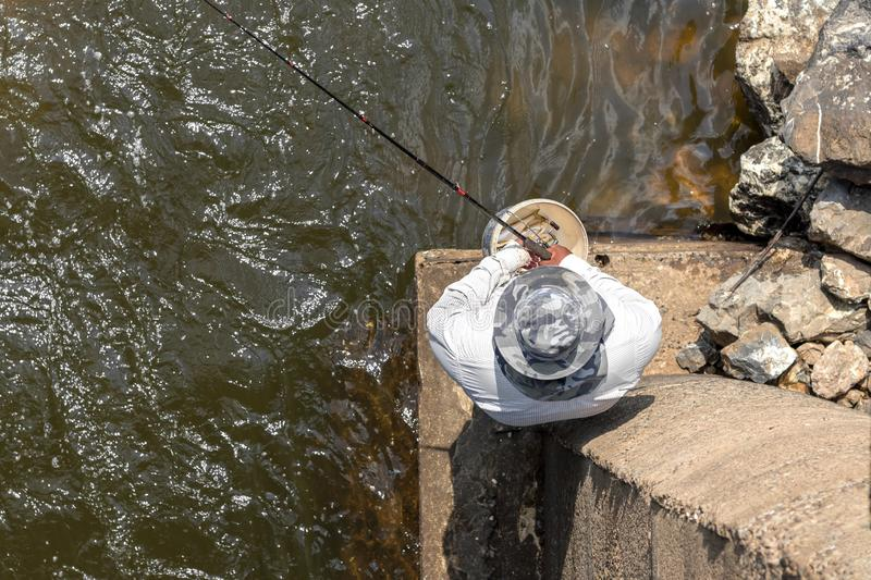 Top view fishing men on concrete sticks. View from the top Close-up of a man wearing a hat, fishing hook, standing on a concrete platform under a bridge on a royalty free stock photo
