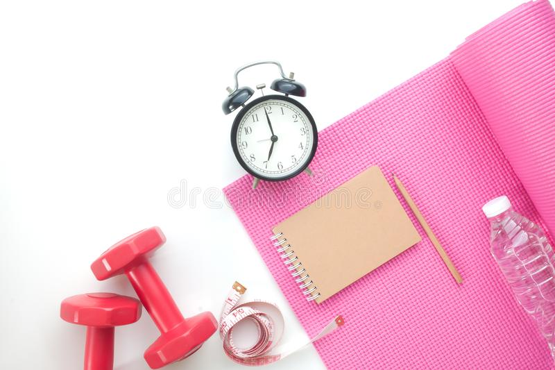 Top view of fitness and yoga equipments with alarm clock and notebook on white background stock photo