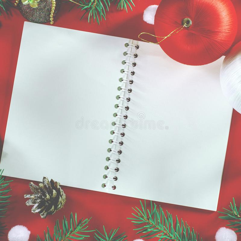 Christmas shopping concept Paper bag full of fir tree and christmas balls with pine cone on red background top view royalty free stock photo