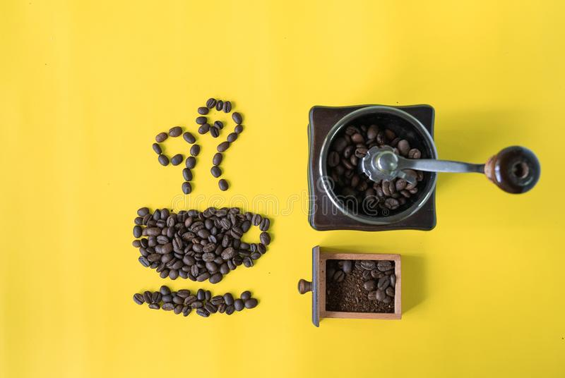 Top view flat lay coffee beans in cup and smell icon shape and vintage wooden coffee grinder on yellow background stock photo