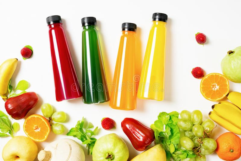 Top view flat lay Colorful juice bottles with ingredients on white background. Healthy lifestyle, vegetarian food concept. Detox royalty free stock images