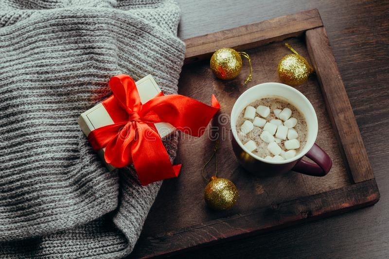 Flat lay cozy holidays festive crd hot chocolate ,gift box and sweater on a wooden tray. Top view flat lay cozy holidays festive crd hot chocolate ,gift box and royalty free stock photography