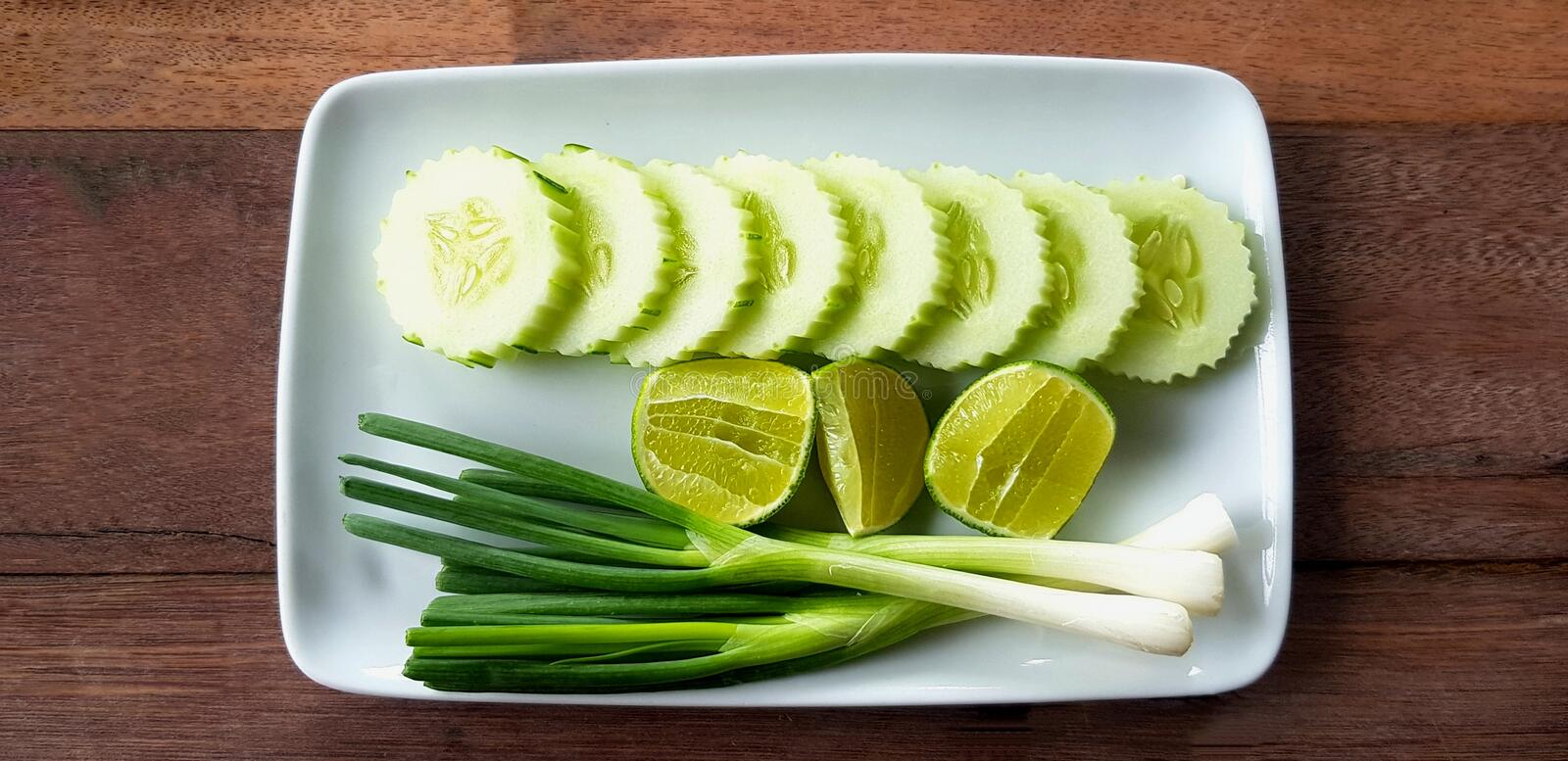 Top view of flat lay of fresh Scallion, sliced cucumber and lime or lemon in white plate on wooden table. Organic vegetable food and Harvest of agriculture royalty free stock images
