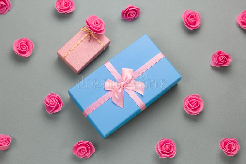 Gift boxes and delicate pink roses pattern on a gray background. Top view flat lay gift boxes and  delicate pink roses pattern on a gray background royalty free stock image