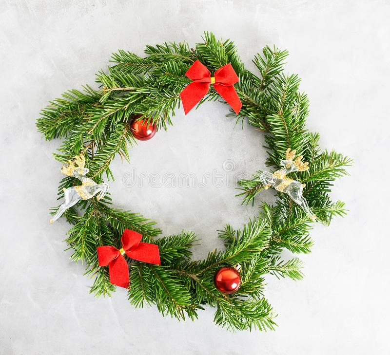 Top view flat lay green Christmas wreath with toys and red bows on bright background. Traditional New year decoration concept royalty free stock images
