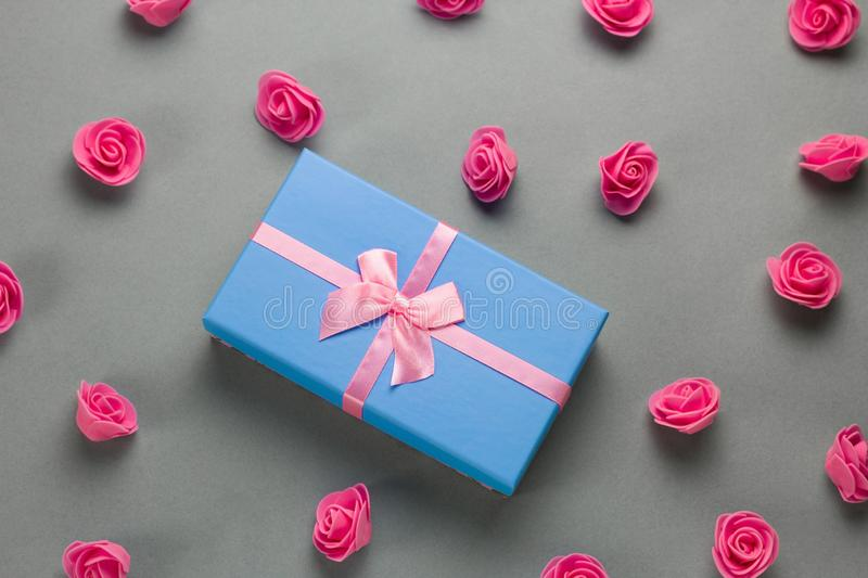Flat lay luxury blue present box with festive pink  satin ribbon bow and delicate pink roses pattern on a gray background. Top view flat lay luxury blue present stock photography