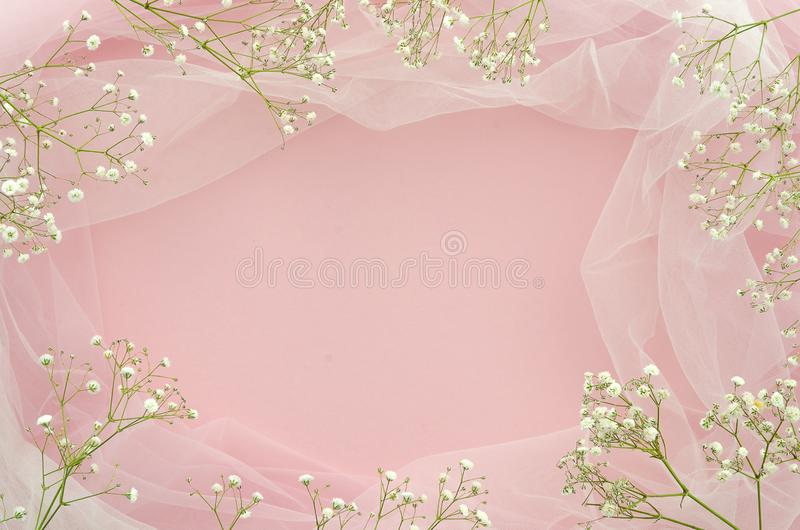 Flat lay wedding concept. Frame made of gypsophila and white tulle on pink background with copy spase for your text stock photography