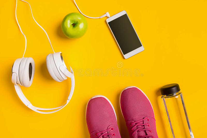 Top view, flat lay. Mockup. Sports and fitness background. Still life of bottle with water, sportswear, apple on yellow background. Top view, flat lay. Mockup stock photo