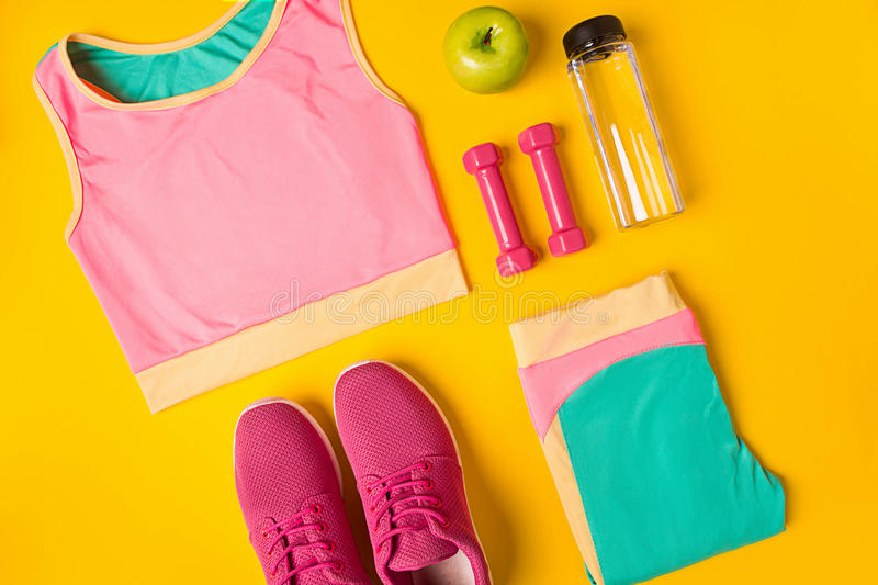 Top view, flat lay. Mockup. Sports and fitness background. Still life of bottle with water, sportswear, dumbbells, apple on yellow background. Top view, flat stock photo
