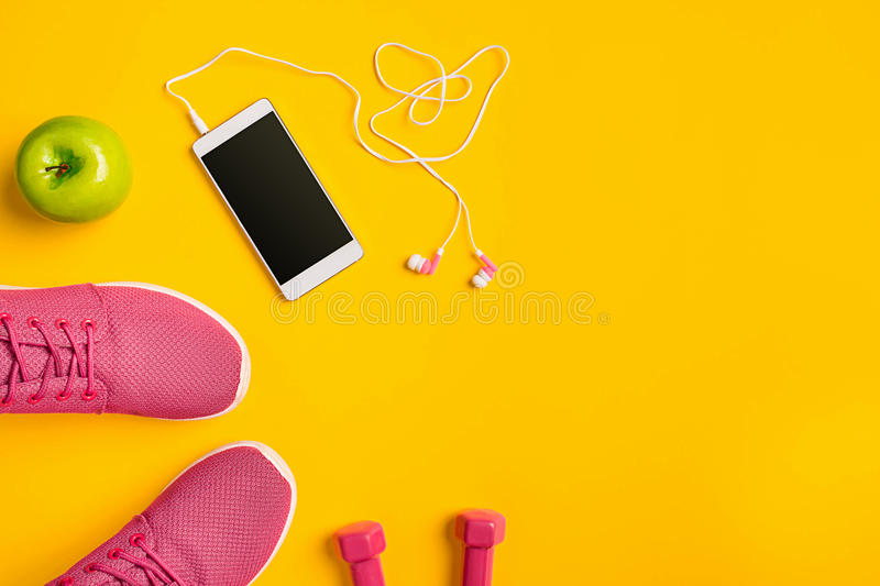 Top view, flat lay. Mockup. Sports and fitness background. Still life of phone with headphones, sneakers, dumbbells on yellow background. Top view, flat lay royalty free stock image