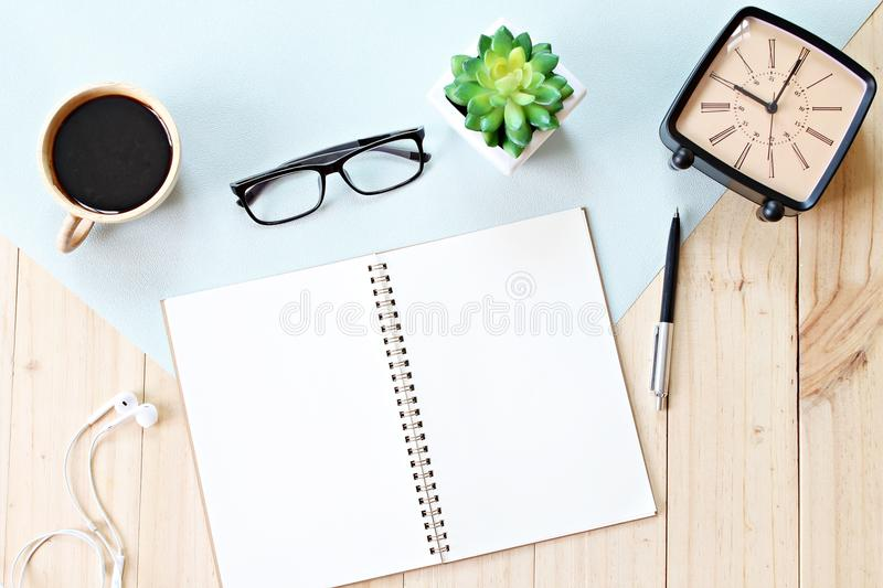 Top view or flat lay of open notebook paper with blank pages, accessories and coffee cup on wooden background, ready for adding or. Still life, business, office royalty free stock photos