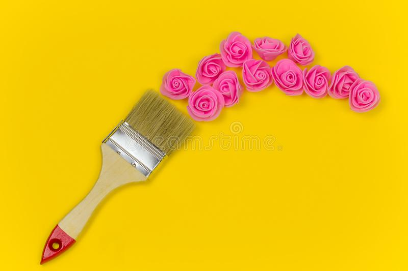 flat lay paint brush with bouquet of rose flowers on vibrant yellow background stock photos