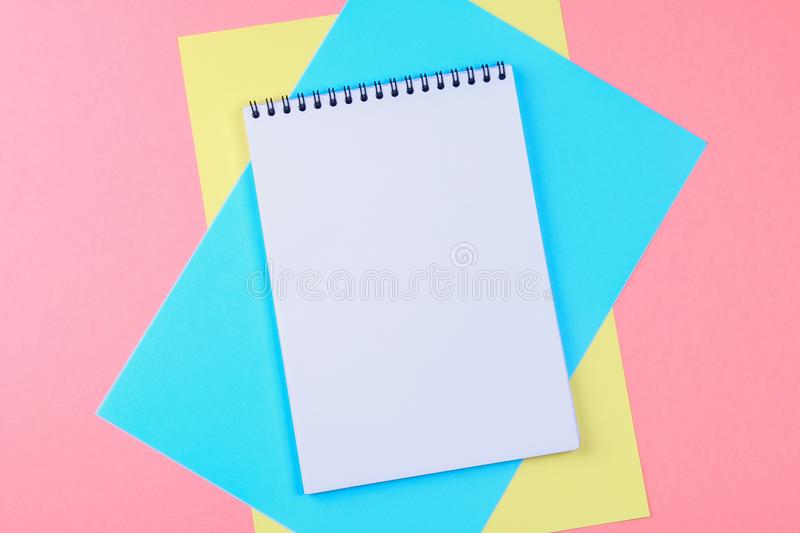 Top view flat lay picture with blank notepad page and different accessories on colored surface. stock image