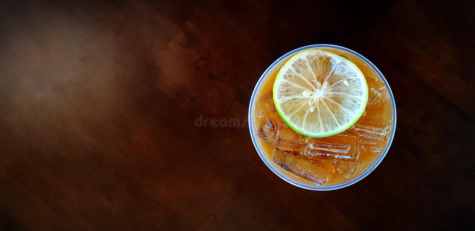Flat lay of plastic glass of iced lemon tea with sliced lime or lemon on top isolated on dark wooden background stock photography