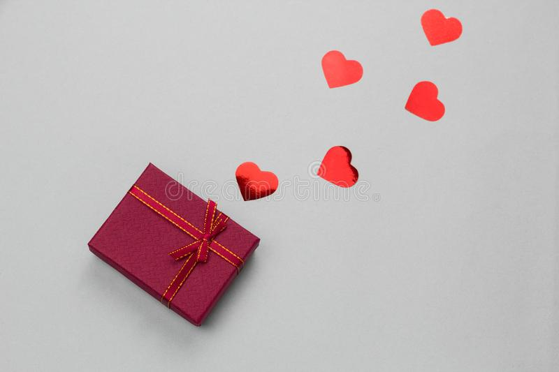 red gift box with red holographic hearts stock images