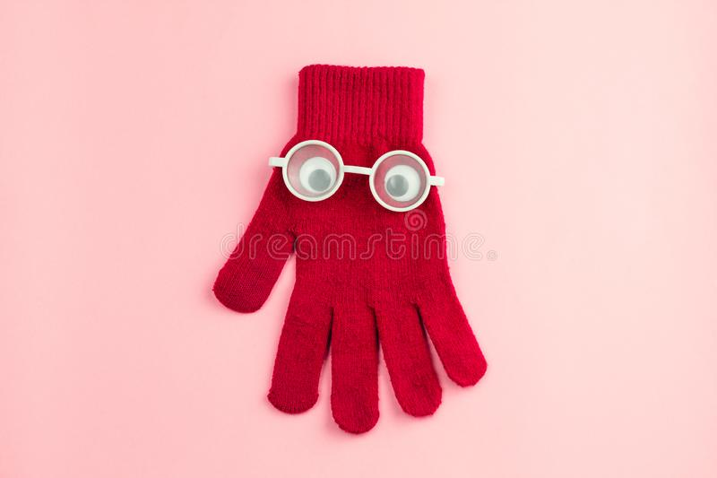 Red glove with googly eyes and white glasses on a pink background. Top view flat lay    red glove with googly eyes and white glasses on a pink background royalty free stock image