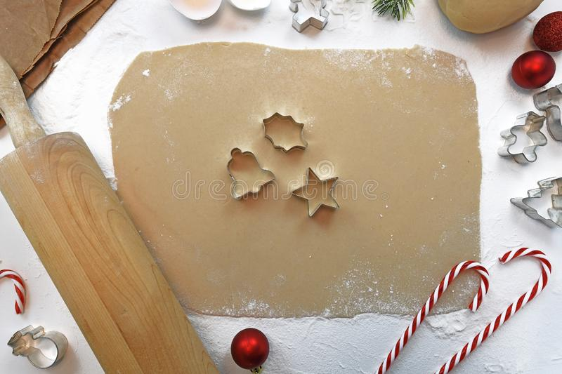 Top view flat lay of rolled out cookie dough with rolling pin, seasonal cookie cutters and Christmas decoration stock photos