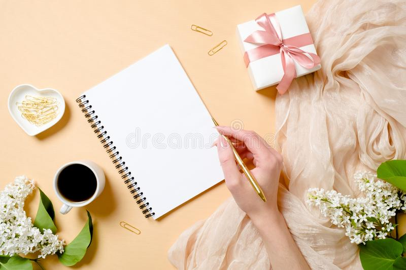 Top view, flat lay women desk with lilac flowers, silk scarf, coffee cup, gift box, human hand holding golden pen and writing in stock images