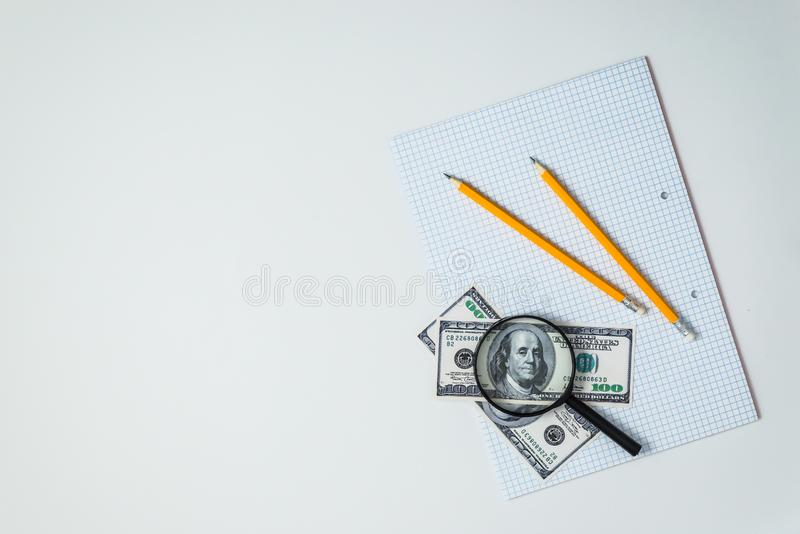 Top view or flatlay of blank sheet of school notebook with pencil and dollars and magnifying glass royalty free stock images
