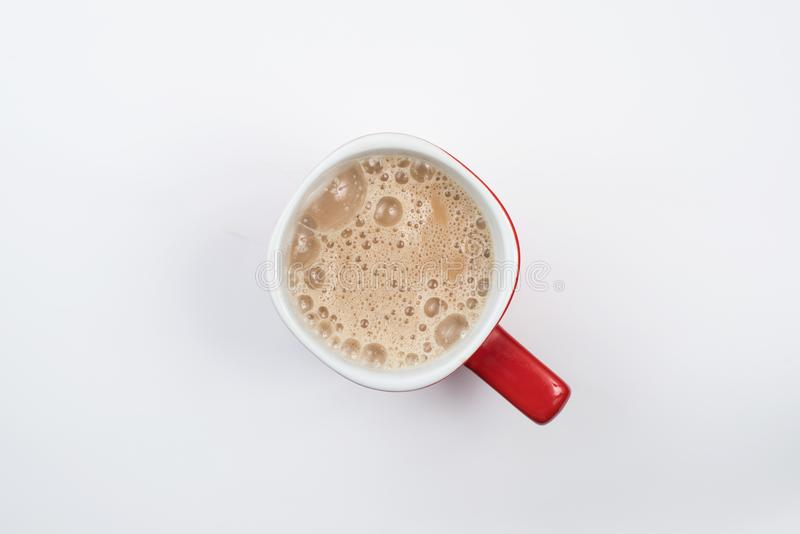 Top view of foamy milk coffee or milk tea in a red mug. On white background stock photo