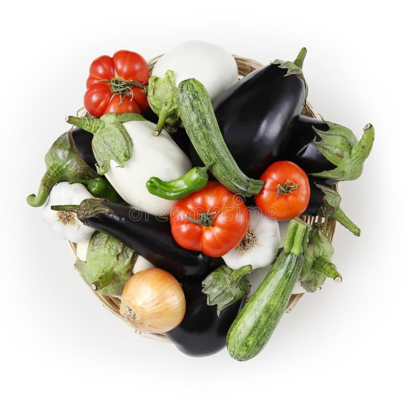 top view food white and black eggplants with tomatoes, zucchini, onion and garlic in wicker, basket isolated on white background royalty free stock photography