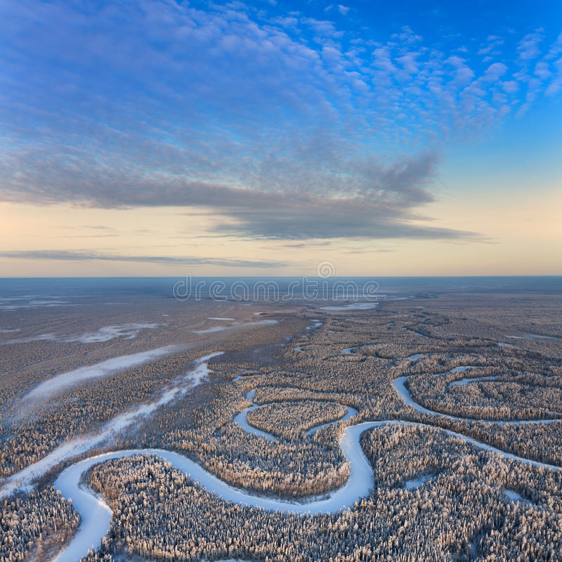 Top view of forest river in winter. Aerial view of forest river during cold winter day. Magnificent hoarfrost is on trees. A winter forest is in a hard frost stock photo