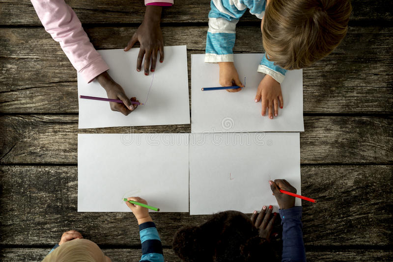 Top view of four children, boys and girls of mixed races, drawing royalty free stock images